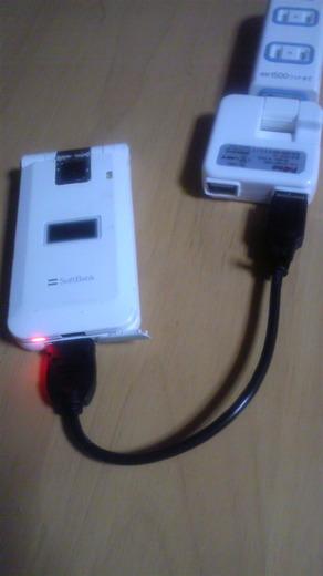 ACアダプターとUSBケーブルで携帯電話を充電中